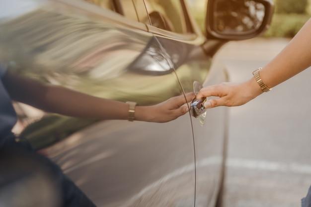 Feche as mãos da mulher usando a chave do sistema perto do carro para desbloquear o carro azul perto da estrada dirigindo