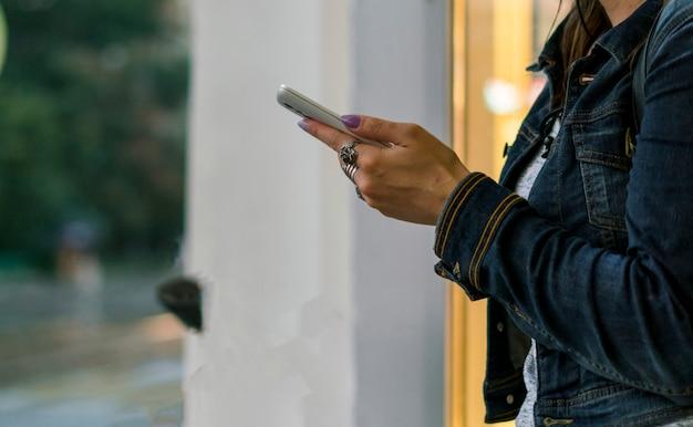 Feche as mãos da mulher usando o celular na cidade em um dia chuvoso
