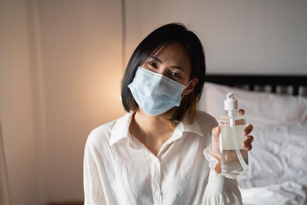 Feche as mãos da mulher usando o dispensador de gel desinfetante para as mãos, contra 2019-ncov em casa.