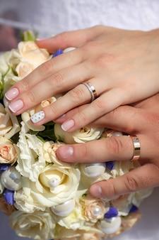 Feche as mãos da noiva e do noivo com buquê de casamento e anéis de ouro