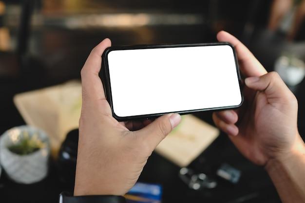 Feche as mãos das mulheres segurando o telefone celular com tela de espaço em branco