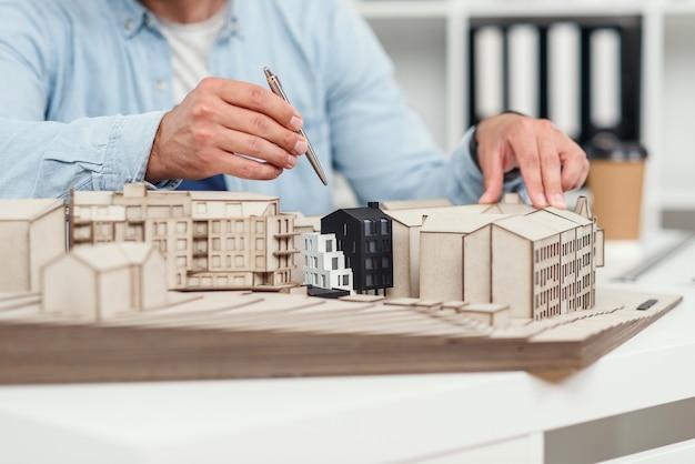 Feche as mãos de arquitetos construindo modelos de edifícios e examina seu trabalho