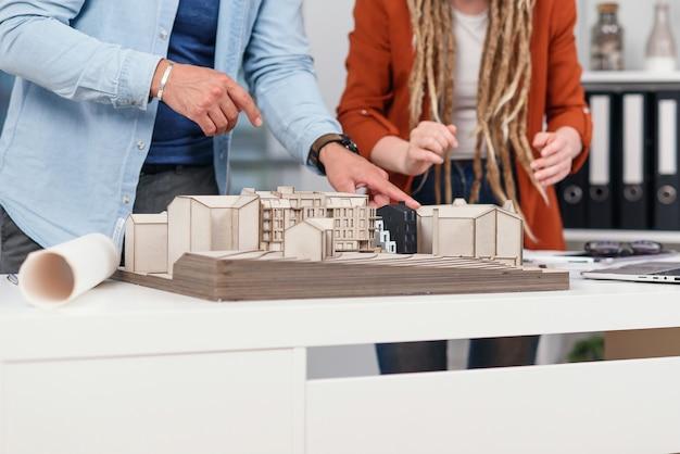 Feche as mãos de arquitetos e arquitetos analisando um projeto conjunto para um futuro complexo residencial