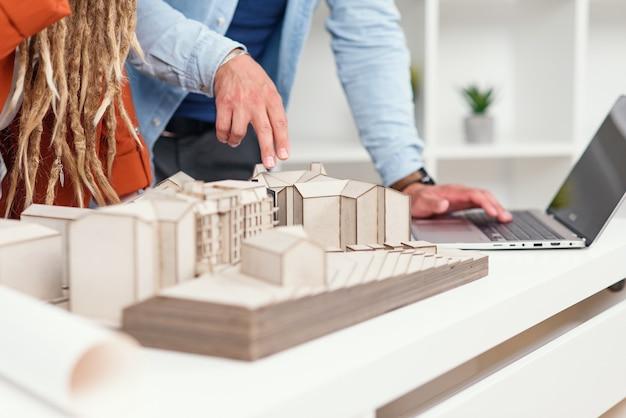 Feche as mãos de arquitetos e arquitetos analisando um projeto conjunto para uma futura área residencial no escritório