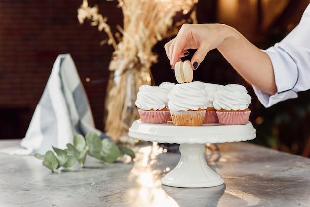 Feche as mãos de confeiteiro feminino colocar um macaron fresco em cima do cupcake com creme.