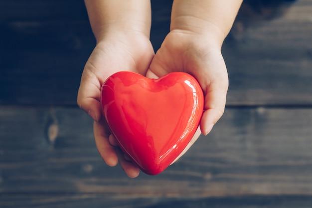 Feche as mãos de crianças dando coração vermelho em fundo de madeira