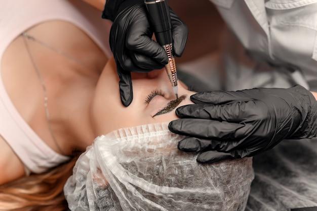 Feche as mãos de esteticista fazendo tatuagem de sobrancelha no rosto de mulher. maquiagem permanente sobrancelha no salão de beleza. especialista em fazer tatuagem de sobrancelha para rosto feminino. tratamento de cosmetologia.