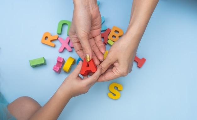 Feche as mãos de mãe e filha estudando o alfabeto