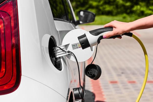 Feche as mãos de mulher, conectando um cabo de alimentação ao carro elétrico para carregar na estação de carregamento ao ar livre.
