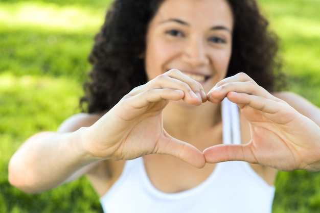 Feche as mãos de mulher de foco mostram símbolo de amor.