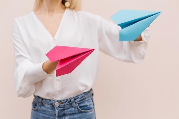 Feche as mãos de mulheres segurando aviões de papel rosa e azul sobre fundo bege.