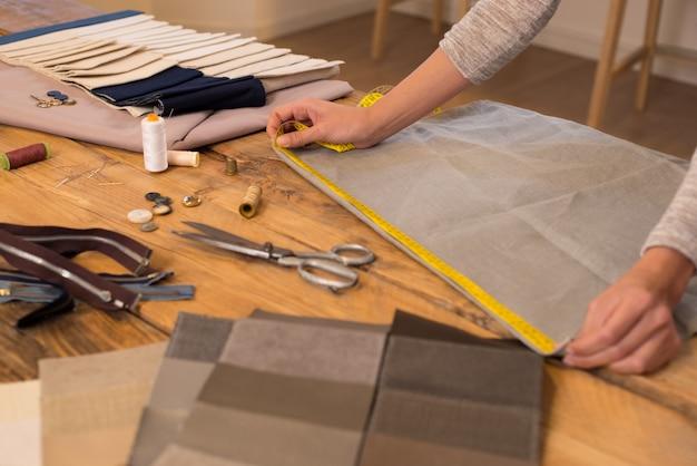 Feche as mãos de um estilista no trabalho com tecido de pano. alfaiate profissional medindo material têxtil. mãos femininas no trabalho com fita métrica para pano novo.
