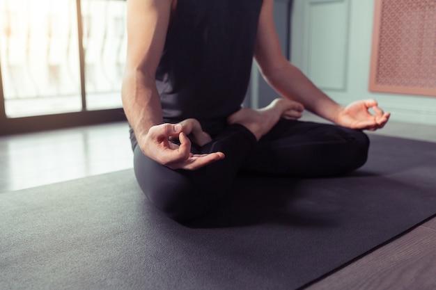 Feche as mãos de um homem fazendo pose de lótus de ioga