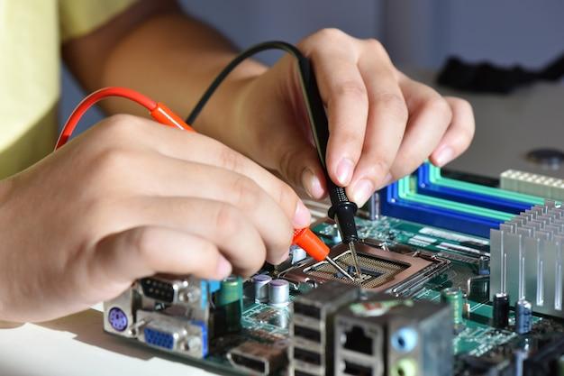 Feche as mãos de um prestador de serviço consertando o computador de placa da cpu