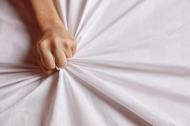 Feche as mãos de uma jovem mulher sexy, puxando lençóis brancos em êxtase no hotel. linda garota fazendo sinal de orgasmo na cama branca (sexo e conceito erótico para propaganda)