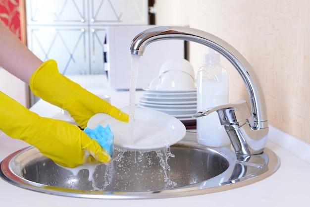 Feche as mãos de uma mulher lavando pratos na cozinha