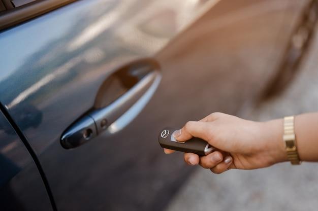 Feche as mãos de uma mulher pressionando a tecla de sistema remoto perto do carro para destravar o carro azul perto da rua