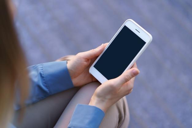 Feche as mãos de uma mulher segurando um smartphone com tela preta