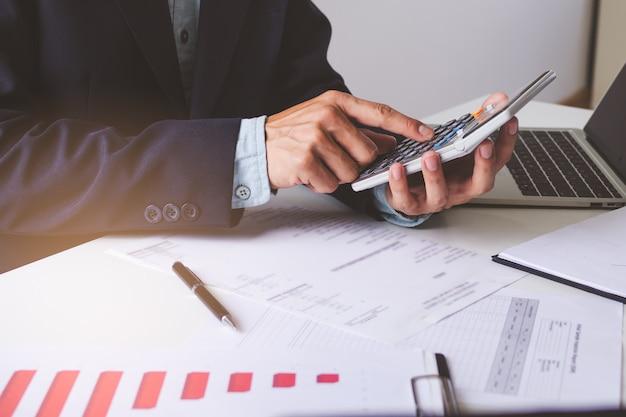 Feche as mãos de vista do empresário usando a calculadora e fazendo contabilidade com gráfico e documentos em cima da mesa.