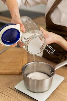 Feche as mãos despejando açúcar na panela