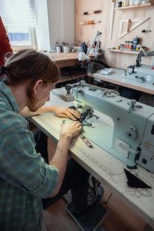Feche as mãos do artesão, costure coisas em branco para usar na carteira, máquina de costura trabalhando em uma oficina de couro