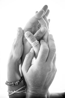 Feche as mãos do casal apaixonado em preto e branco. casal de mãos dadas. mãos de casal apaixonado com anel e pulseira sobre fundo branco
