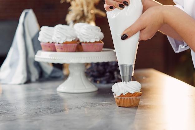 Feche as mãos do chef feminino com saco de confeitaria, espremendo o creme em cupcakes.