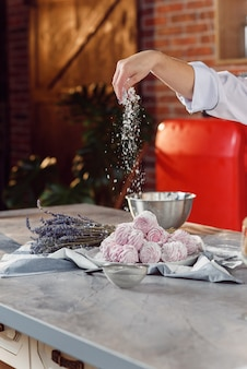 Feche as mãos do chef polvilha marshmallows caseiros com açúcar em pó. processo de preparação de marshmallow. o conceito de cozinha caseira.