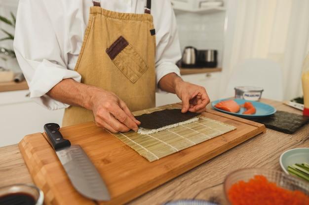 Feche as mãos do chef preparando rolos de sushi japonês, preparando alga nori e arroz em uma mesa