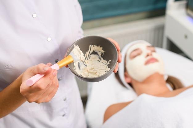 Feche as mãos do cosmetologista com uma escova e uma máscara de argila facial espessa