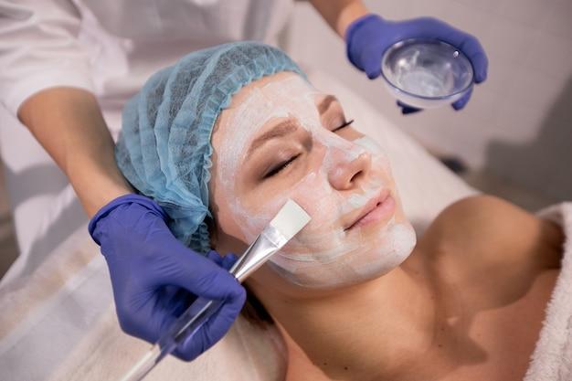 Feche as mãos do cosmetologista em luvas azuis, aplicando uma máscara médica no rosto do paciente com um pincel