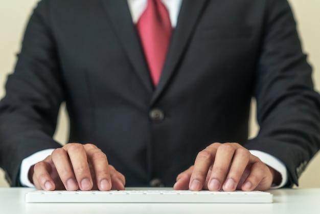 Feche as mãos do empresário vestindo terno preto, digitando o teclado branco sem fio. o encabeçamento do indivíduo asiático do negócio escreve o email no pc do computador no conceito dos povos do gerente, do executivo ou da lei profissional.