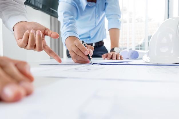 Feche as mãos do engenheiro discutindo um projeto de construção do prédio no local de trabalho