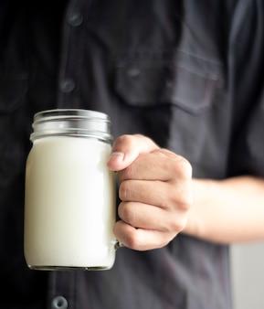Feche as mãos do homem de camisa preta, segurando um copo de leite fresco.