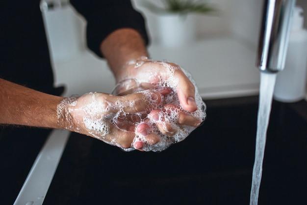 Feche as mãos do homem em espuma de sabão. lavar os dedos e as palmas das mãos e limpá-los. molhe o derramamento da torneira na pia na cozinha. cuidados e proteção das mãos. cara usa camisa preta.