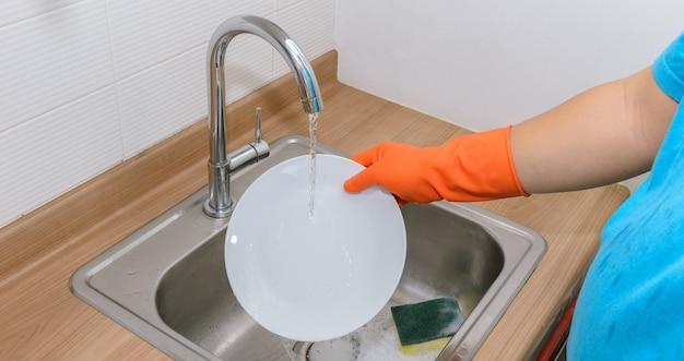 Feche as mãos do homem lavando pratos