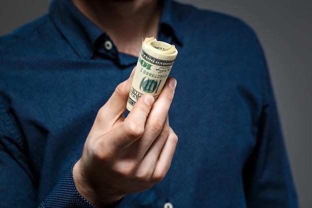 Feche as mãos do homem segurando o dinheiro.