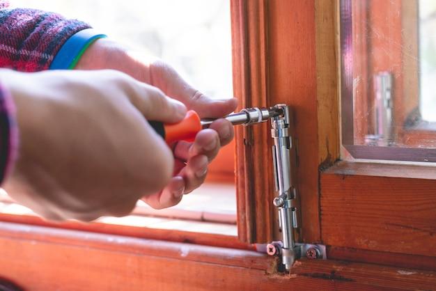 Feche as mãos do homem trabalhando ajustando a trava do parafuso de aço em uma janela de madeira f