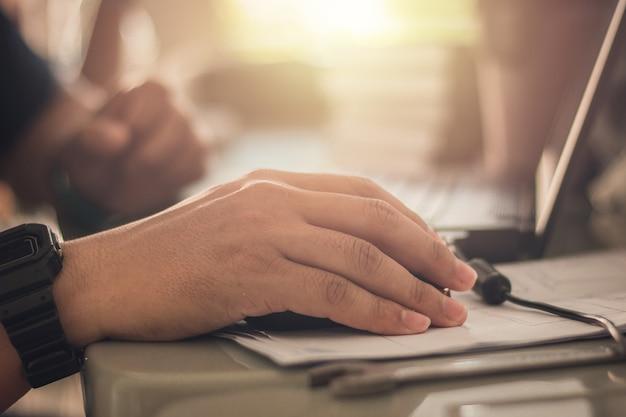 Feche as mãos do homem use o mouse está trabalhando no computador ou laptop