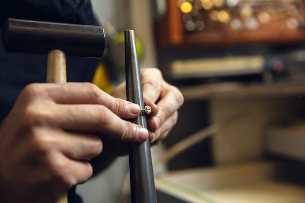 Feche as mãos do joalheiro, ourives fazendo anéis de ouro com pedras preciosas usando ferramentas profissionais
