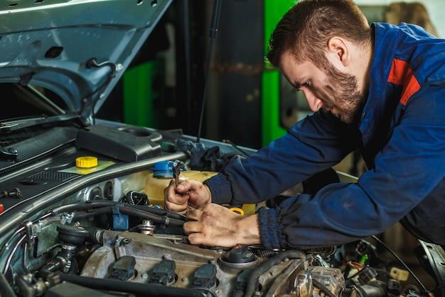 Feche as mãos do mecânico irreconhecível, fazendo manutenção e serviço de carro