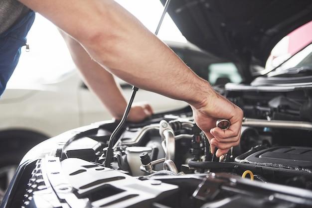 Feche as mãos do mecânico irreconhecível, fazendo serviço e manutenção do carro.