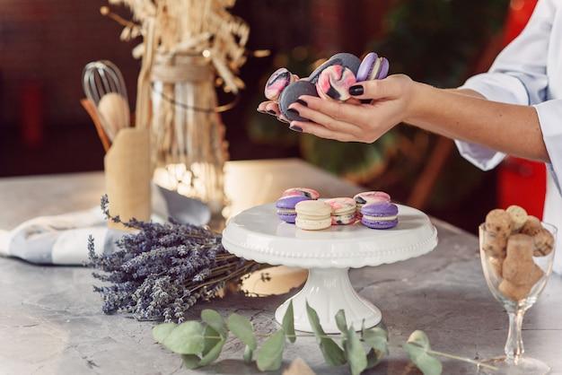 Feche as mãos do padeiro feminino com manicure preto segurando biscoitos franceses coloridos sobre uma mesa de mármore com um prato, lavanda e eucalipto.