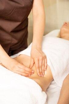 Feche as mãos do quiroprático ou massagista fazendo massagem relaxante de estômago para a mulher deitada no interior da clínica.