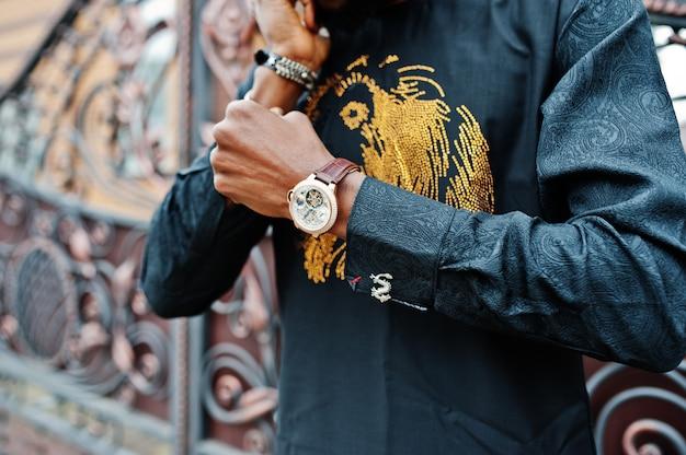 Feche as mãos do rico homem africano com relógio e abotoaduras.