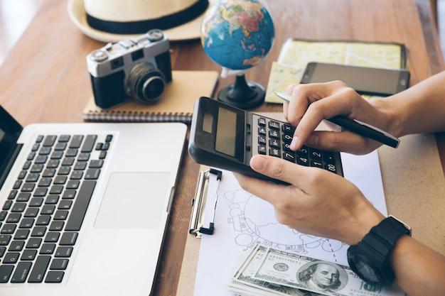 Feche as mãos dos viajantes usando uma calculadora para calcular as despesas de viagem. planejando uma viagem, copie o espaço. fundo de viagens