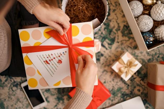 Feche as mãos femininas amarrando um laço de fita vermelha em uma caixa de presente de artesanato.