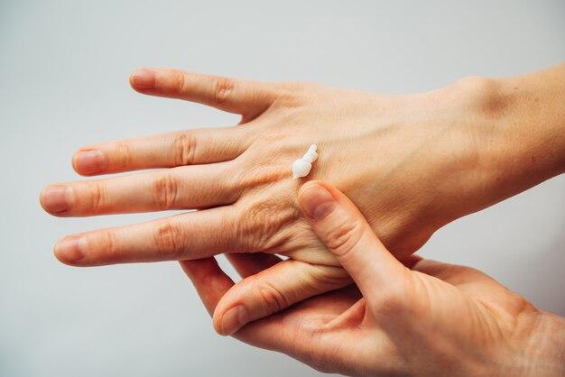Feche as mãos femininas aplicando loção cosmética hidratante, em branco