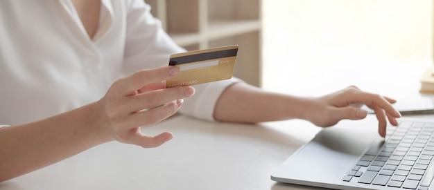 Feche as mãos femininas segurando um cartão de crédito e smartphone, jovem pagando online, usando o serviço bancário, inserindo informações, fazendo compras, fazendo pedidos na loja da internet, fazendo o pagamento seguro