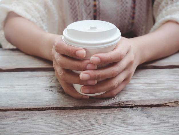 Feche as mãos femininas segurando um copo de papel de café branco na mesa de madeira. jovem mulher bebendo café do copo descartável.